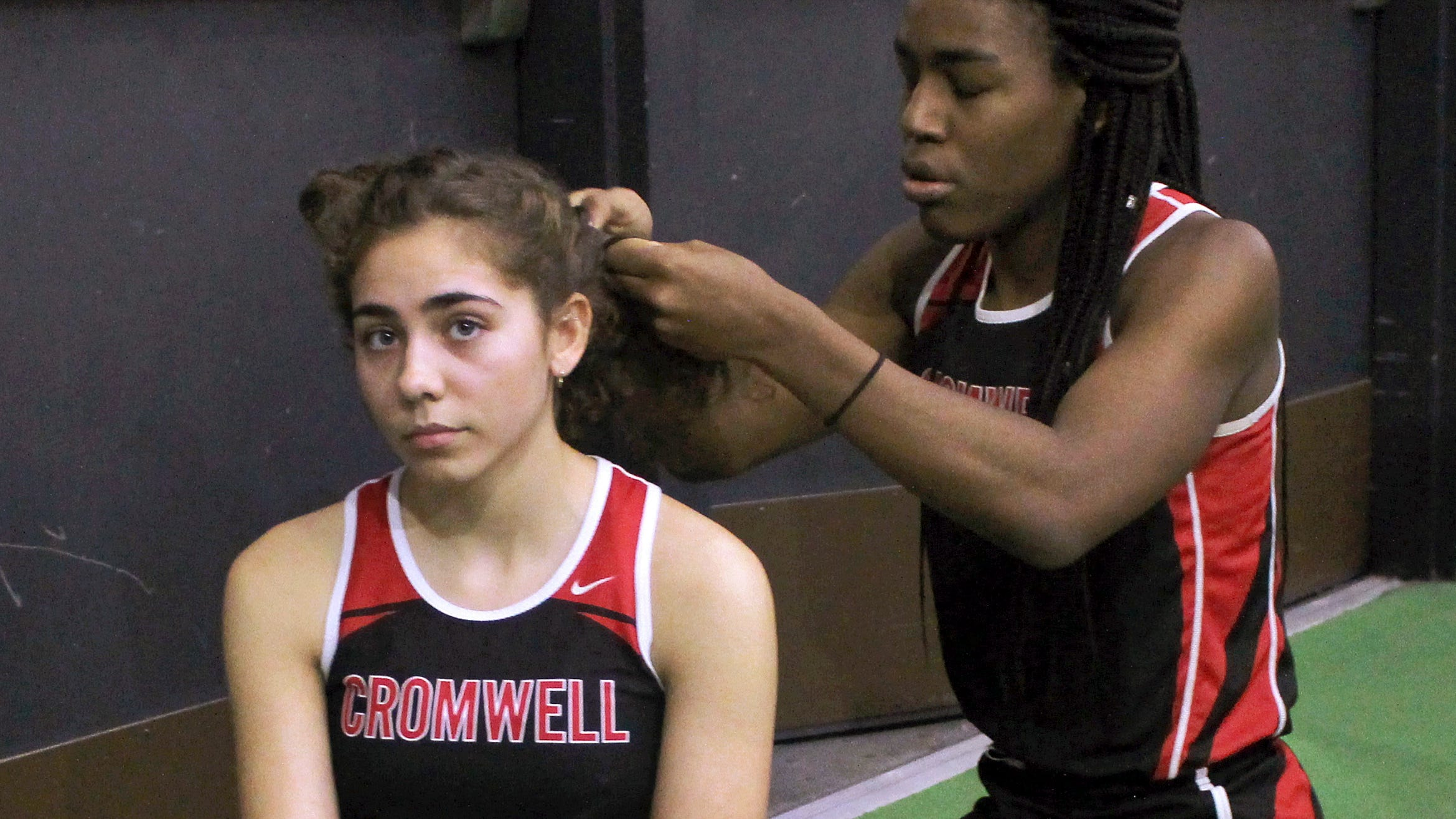 In this Feb. 7, 2019 file photo, Cromwell High School transgender athlete Andraya Yearwood, right, braids the hair of teammate Taylor Santos during a break at a track meet at Hillhouse High School in New Haven, Conn.