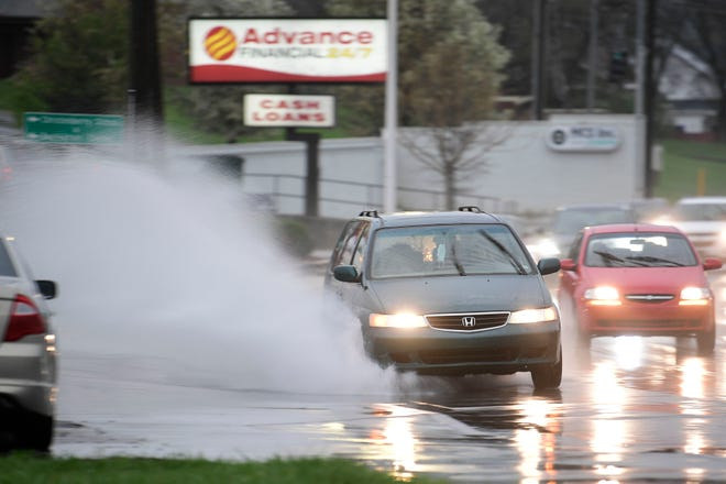 Vehicles drive through standing water on Broadway during a rainstorm in Knoxville, Tenn. on Thursday, March 25, 2021.