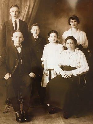 William Schaefer, baker, and his family are shown in this circa 1920 photo. William Schaefer is seated on left and his wife Augusta is seated on right. Back row (L to R) are son Eugene, son George and his twin sister Martha, and daughter Cora.