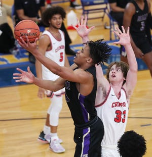 Male's Kaleb Glenn (1) shoots against Manual defenders during their game at Valley High School in Louisville, Ky. on Mar. 24, 2021.