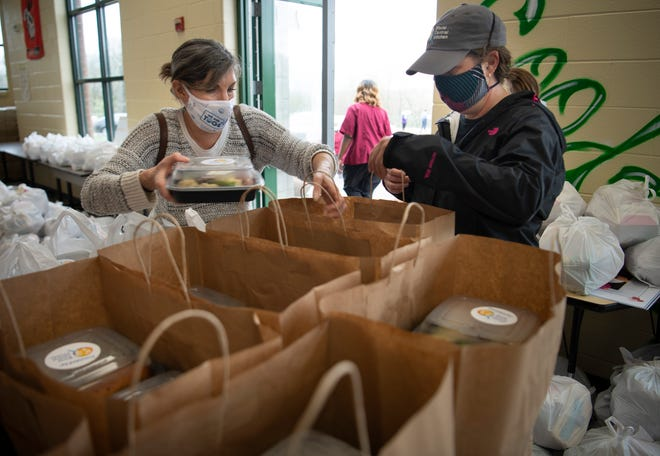 Deborah Oleshansky of the Jewish Federation of Nashville and Middle Tenn. and Whitney Pastorek of World Central Kitchen pack cooked meals from Shugga-Hi Bakery and Cafe for distribution to families at Jere Baxter Middle School  Thursday, March 25, 2021 in Nashville, Tenn.