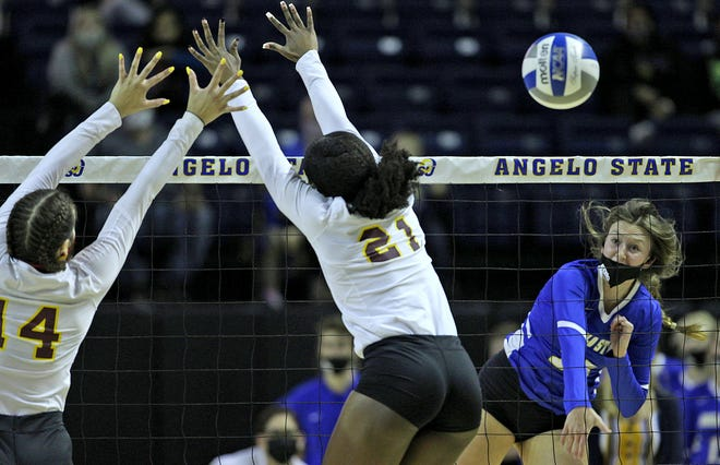 Delaney Fuller, far right, spikes the ball for Angelo State during a game against Midwestern State on Wednesday, March 24, 2021.