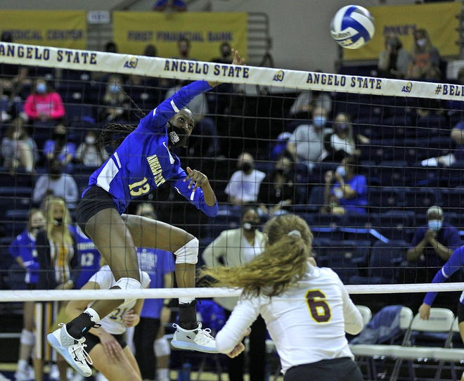 Grace White, left, spikes the ball for Angelo State during a game against Midwestern State on Wednesday, March 24, 2021.