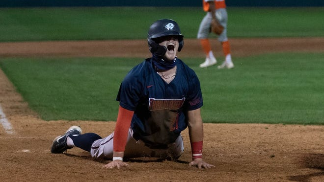 Dixie State's Kaden Hollow celebrates after sliding into home plate during a game against Texas Rio Grande Valley.