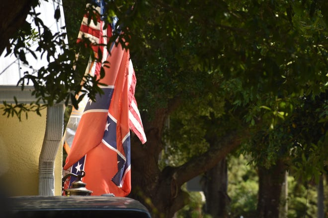 A confederate flag hangs in front of a house.