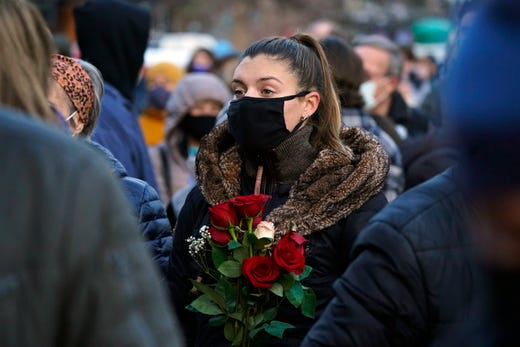 A mourner holds a bouquet of roses at a vigil for the victims of a mass shooting in a grocery store, Wednesday, March 24, 2021, outside the courthouse in Boulder, Colo.