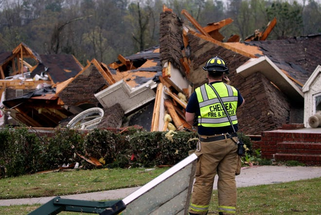 A firefighter is pictured surveying damage to a house after an apparent tornado touched down near Birmingham, Alabama, on Thursday. Authorities reported major tornado damage south of Birmingham as strong storms moved through the state.