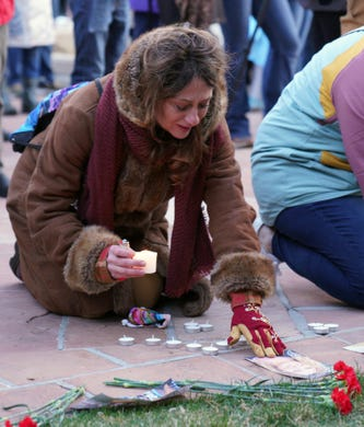 An attendee at a vigil to remember the 10 killed in Monday's shooting at a King Soopers grocery store in Boulder, Colo., lights a candle and touches the name of one of the dead.