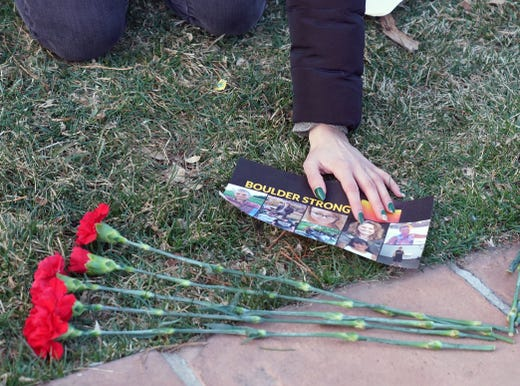 An attendee at a vigil to remember the 10 killed in Monday's shooting at a King Soopers grocery store in Boulder, Colo, lays out flowers and a sign. .