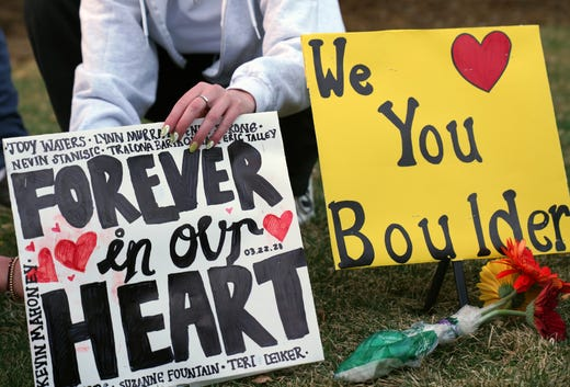 An attendee at a vigil to remember the 10 killed in Monday's shooting at a King Soopers grocery store in Boulder, Colo., sets out a sign.