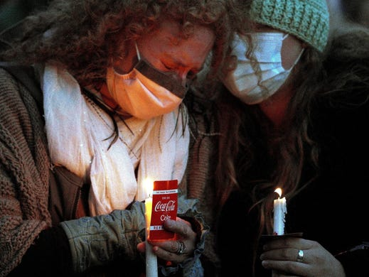 Jill Ascher, left, is comforted by a friend at a vigil to remember the 10 killed in Monday's shooting at a King Soopers grocery store in Boulder, Colo. Ascher was friends with Tralona Bartkowiak, 49, one of the dead, who owned a store on the Pearl Street Mall, just a few steps from where the vigil was held.