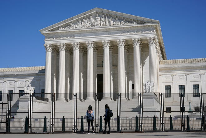 People view the Supreme Court building from behind security fencing on Capitol Hill in Washington, Sunday, March 21, 2021, after portions of an outer perimeter of fencing were removed overnight to allow public access. (AP Photo/Patrick Semansky) ORG XMIT: DCPS105