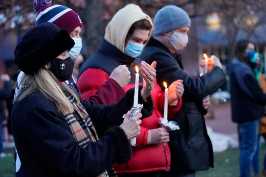 Mourners shield the flames of their candles from the wind at a vigil for the victims of a mass shooting at a grocery store earlier in the week, Wednesday, March 24, 2021, outside the courthouse in Boulder, Colo.