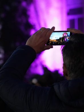 A man takes a video of a vigil to remember the 10 killed in Monday's shooting at a King Soopers grocery store in Boulder, Colo.
