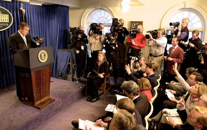 """President George W. Bush calls on a reporter during his first news conference at the White House on Feb. 22, 2001, in Washington.  The president spoke at his first White House news conference a month after his inauguration. He said one of his early goals was to """"change the tone""""' in Washington and """"encourage civil discourse. I think we're making good progress.''"""
