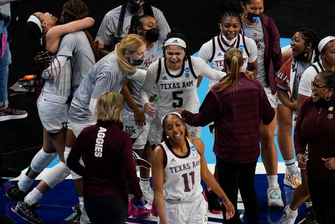 Jordan Nixon celebrates with teammates after beating the buzzer in overtime to give Texas A&M the win over Iowa State.