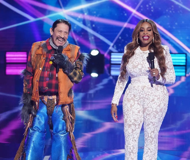 On the March 24 episode of Fox's 'The Masked Singer,' Raccoon, the latest eliminated contestant, was revealed to be Danny Trejo, left. He was joined on stage by host Niecy Nash.