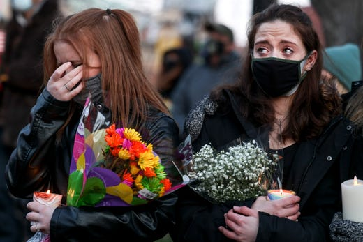 Maxene McNice, left, and Hailey Calcagno attend a candlelight vigil outside the Boulder County Courthouse on March 24, 2021 in Boulder, Colo. Ten people, including a police officer, were killed in a shooting at a King Soopers grocery store nearby on Monday.