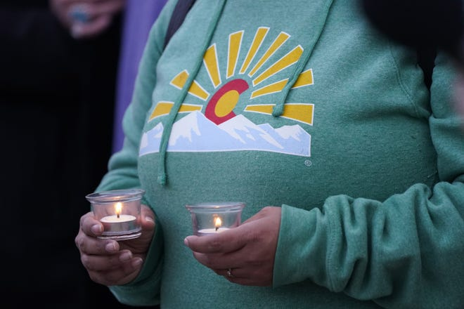A mourner holds candles at a vigil for the 10 victims of the Monday massacre at a King Soopers grocery store late Thursday, March 25, 2021, at Fairview High School in Boulder, Colo. (AP Photo/David Zalubowski)