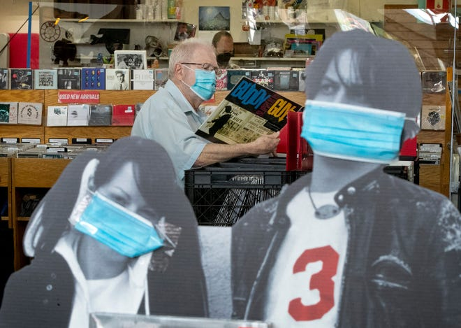John Runde, of Bristol, Tenn., shops at Waterloo Records while wearing a mask on March 26. [AMERICAN-STATESMAN/FILE]