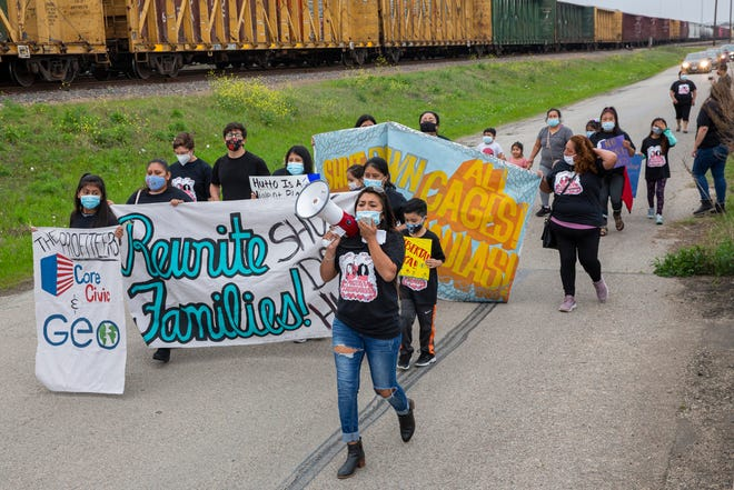 Sulma Franco, a Guatemalan immigrant and activist, leads a group of people Wednesday toward the T. Don Hutto Residential Center in Taylor. Groups, families and residents marched, along with a car rally, to demand the Biden administration shut down the detention center, saying it is not safe for women and families held there.