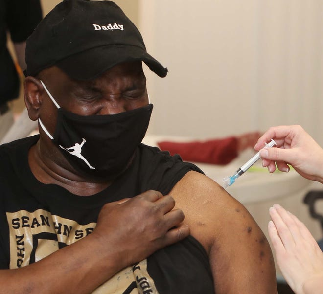 Cornell Johnson, a resident at Collinson Apartments in Akron, winces as he receives his COVID-19 vaccination Friday. Many residents at the apartments are homebound.