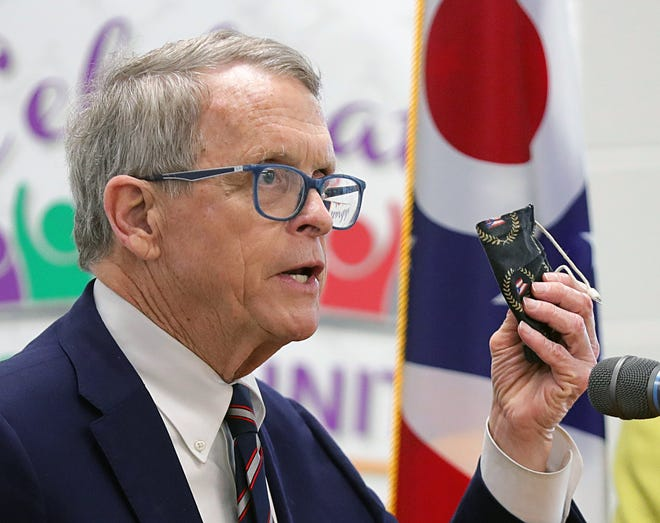 Gov. Mike DeWine holds up his mask as he fields questions during a press conference at a vaccine clinic Friday in Plain Township. Later in the day, he toured the Jewish Senior Housing of Akron, where the National Guard vaccinated residents and others during a pop-up clinic.