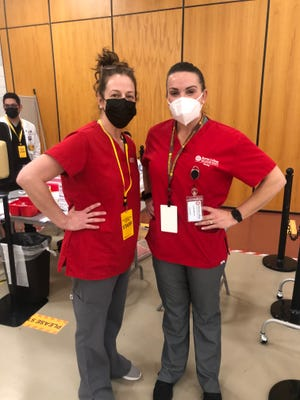 Medford woman Lee Cohen, left, with a fellow nurse, Lauren Wolicki, right, at the Rowan School of Medicine vaccination site in Stratford.