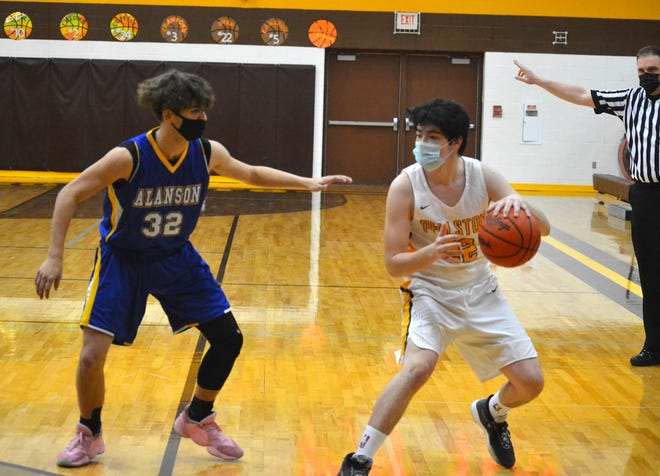 Pellston sophomore guard Coby Dyer (right) looks to get past Alanson senior guard James Hungo during the first half of a Division 4 boys basketball district final in Pellston on Thursday.