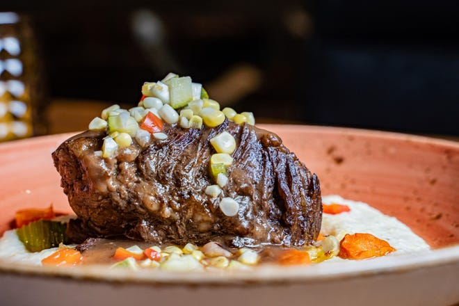 Beef short ribs served with braised vegetables over creamy grits and chow chow