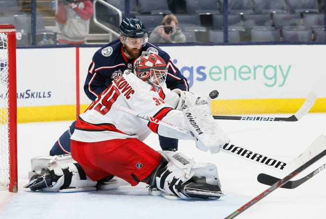 Carolina Hurricanes goaltender Alex Nedeljkovic (39) makes a stop on a point blank shot from Columbus Blue Jackets left wing Nick Foligno (71) during the third period of the NHL hockey game in Columbus on Thursday, March 25, 2021.