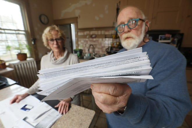 William Martin, 74, of Zanesville, holds up a stack of ReliCards, which are loaded with unemployment benefits. Martin and his wife Catherine are victims of identity theft.
