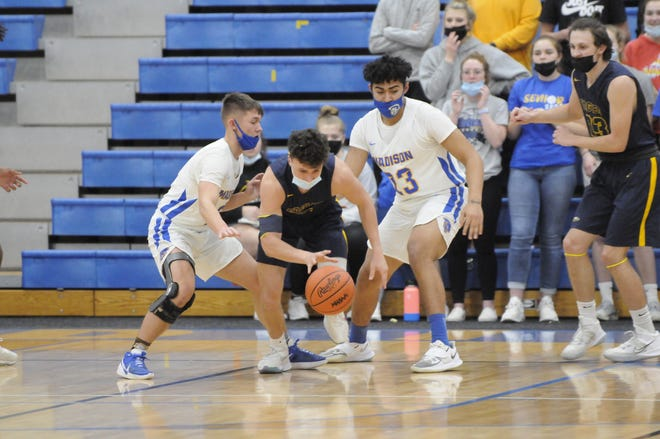 Madison's Max Palpant (left) and Marcel Theriot (right) guard Erie Mason's Tanner Herrera during Thursday's Division 3 district semifinal.