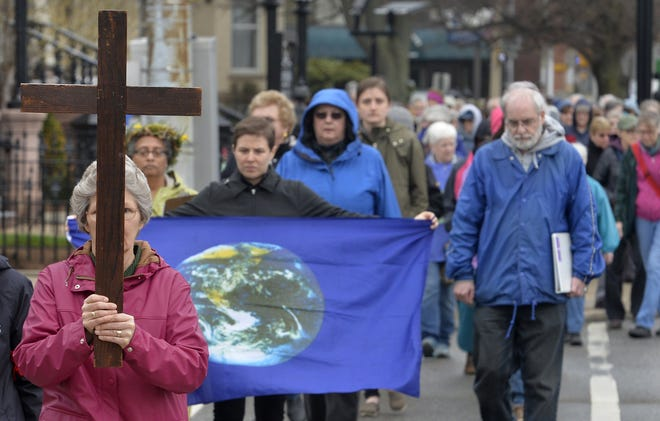 About 100 marchers, led by Erie Benedictine Sister Anne Wambach, with cross, begin the annual Good Friday Pilgrimage for Peace heading south on Sassafras Street from West 10th Street in Erie on April 19, 2019.
