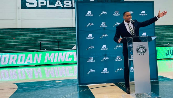 New Jacksonville University basketball coach Jordan Mincy gestures to the new practice facility under construction during Friday's news conference at Swisher Gym.