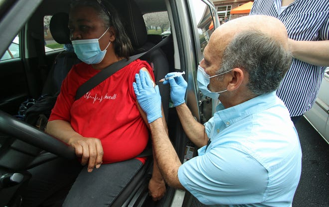 Thomasine Lawrence is given a COVID-19 vaccination shot from pharmacist Jeff Nunnery Friday morning, March 26, 2021, in the parking area at Shelby Drug on East Grover Street in Shelby.