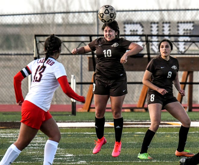 Garden City High School's Destiny Rojo, center, steals a Liberal pass off her head and moves it to a teammate Thursday at Buffalo Stadium during the Buffaloes home opener.  GCHS' Alessandra Tovar is shown at right.