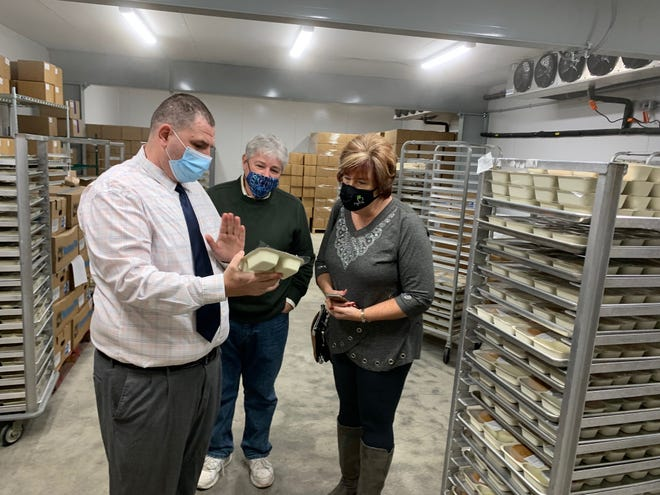 Jay Varnes, director of Meals on Wheels, gives Scott and Sue Neil a tour of the opeartion's kitchen in Massillon. the kitchen was recently named the Neil Family Kitchen after the Alliance couple made a donation to the program.