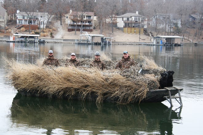 Mark, Blake, Dylan and Tyler Charlton on their duck hunting boat at Lake of the Ozarks. Their black labs, Harper and Diesel, received specialized training to retrieve ducks from the water.