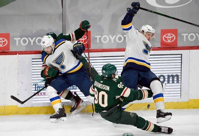 St. Louis Blues' Jake Walman (46) pins Minnesota Wild's Matt Dumba (24) to the boards as Wild's Marcus Johansson (90) and St. Louis Blues' Vladimir Tarasenko (91) fall to the ice during the first period of an NHL hockey game Thursday, March 25, 2021, in St. Paul, Minn.
