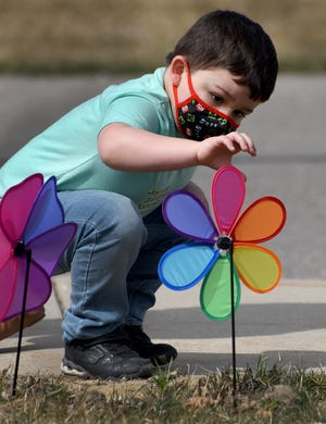 Sterling Elementary preschooler Atticus Messer, 4, watches closely as the pinwheel attempts to spin after placing it into the ground outside Sterling Elementary in Carleton this past Thursday. The event was part of the Child Advocacy Network of Monroe County, who provided the colorful pinwheels which represents healthy happy childhood.
