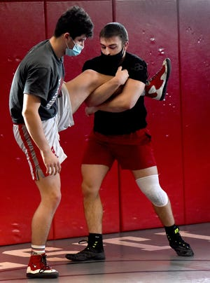 """Bedford senior Drew Grup and junior Randy Boisselle are the only two Bedford Mules wrestlers who are still competing in the wrestling championships due to COVID-19. """"This wrestling room would be packed right now,"""" said coach Kevin Vogel."""