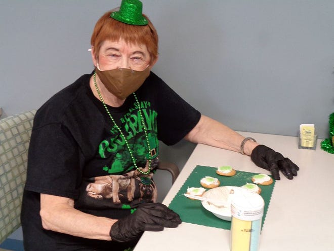 Horizons resident Carole Flint decorates cookies for St. Patrick's Day.