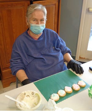 Horizons resident Bev Dean lines up cookies to frost for St. Patrick's Day.