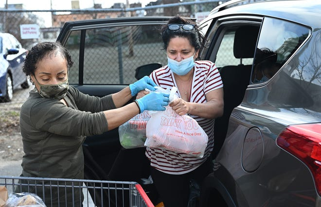 Clara Rodriguez, left, a supervisor, helps Geralda Ramalho, of Worcester, load her car with a month's supply of groceries at the United Way of Tri-County Pearl Street Cupboard and Cafe in Framingham, March 26, 2021.
