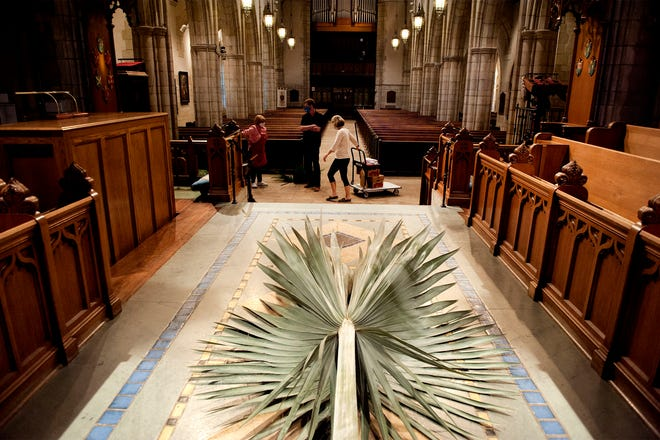 Maury Wolfe, Fred Staley and Sara Griffen decorate The Church of Bethesda-By-The Sea Thursday with palm fronds for the recording of the online Palm Sunday Liturgy and Holy Eucharist service. Because of the coronavirus pandemic, in-person worship will be held outdoors.