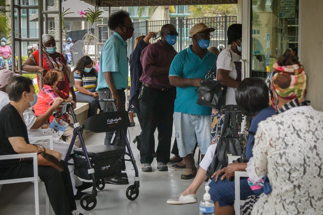 Residents wait in line during a COVID-19 vaccination event at Lake Delray Apartments in Delray Beach, Fla., on Wednesday, March 3, 2021.