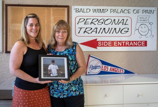 Debi Goldman, left and her mom, Paula Goldman, hold a picture of Neil Goldman in his personal training room at their home in Boynton Beach, Florida on March 26, 2021.