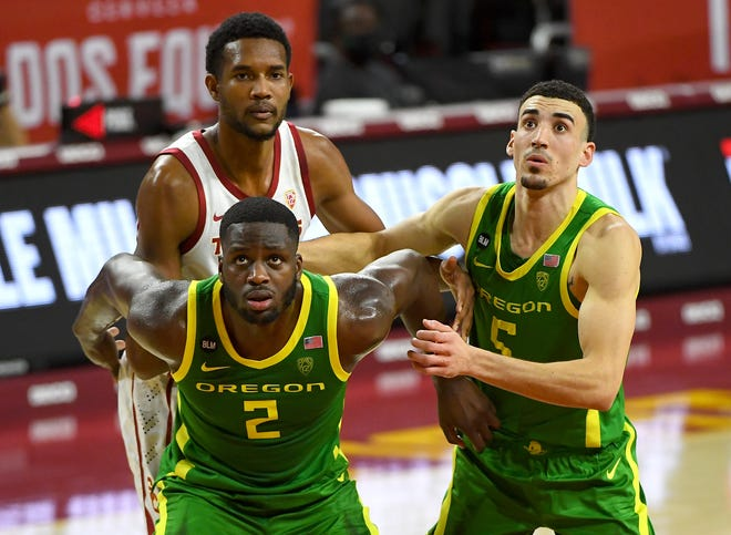 Oregon's Eugene Omoruyi (2) and Chris Duarte (5) box out USC's Evan Mobley during the first half of their Feb. 22 game at the Galen Center in Los Angeles. USC won 72-58.