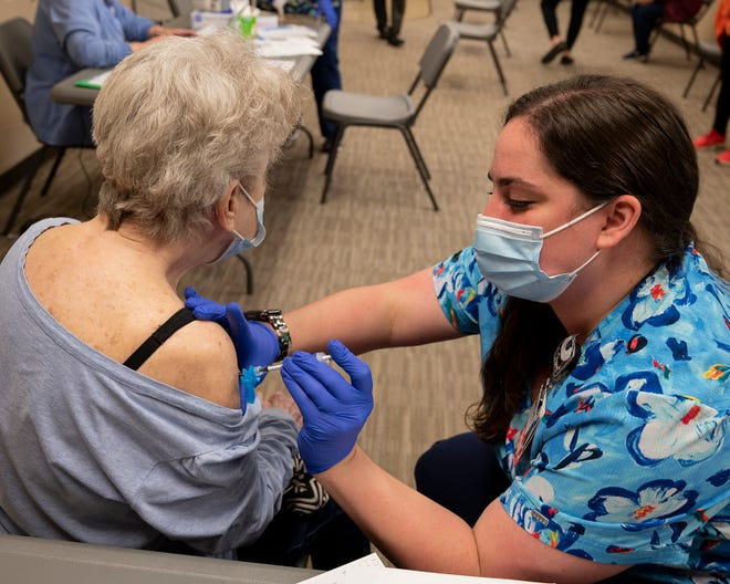 Helen Stinard of Canton gets a COVID-19 vaccine from Cleveland Clinic Mercy Hospital nurse Raechel Gill on Friday at the Mercy at  St. Paul Square Clinic.